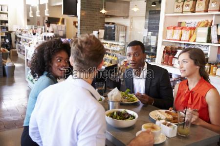 group enjoying business lunch in delicatessen