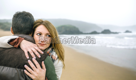 woman embracing man on the beach