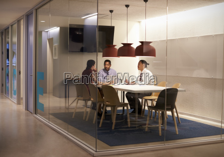 three people in meeting cubicle at