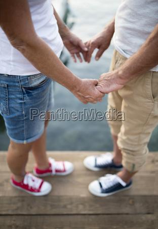 senior couple holding hands on jetty