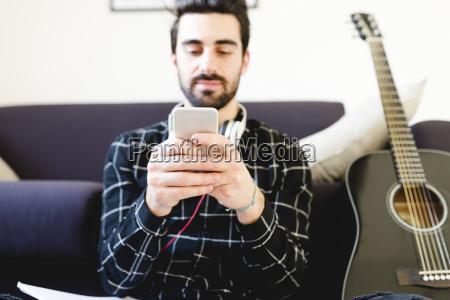 junger mann zu hause mit gitarre