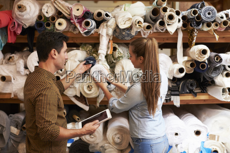 man and woman selecting fabric from