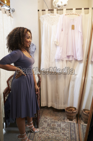 smiling woman trying on dress in