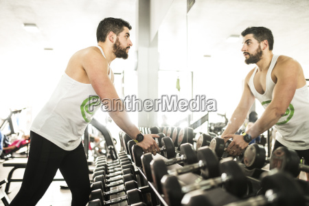 man in gym looking in mirror