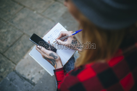 tattooed womans hand writing in notebook