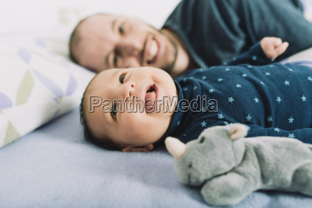 happy father lying in bed with