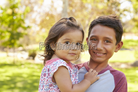 smiling boy carrying his little sister