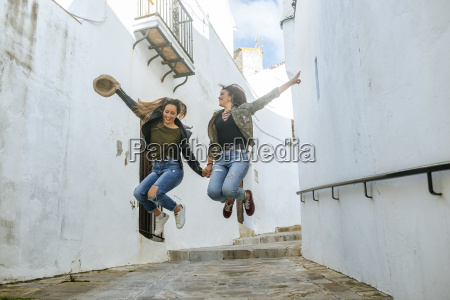 two happy young women jumping in
