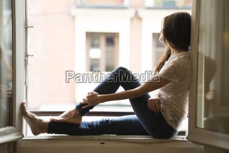 woman sitting on window sill looking