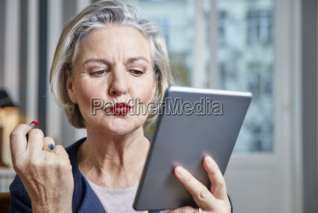 senior woman applying lipstick holding tablet