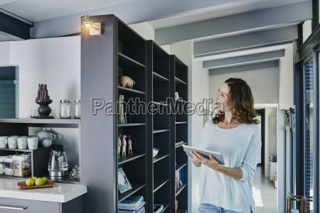 woman regulating lamp with digital tablet