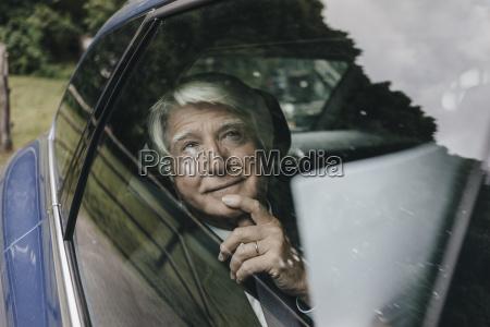 portrait of senior businessman looking through