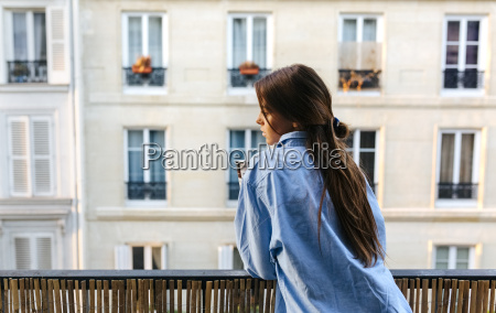 young woman standing on balcony holding