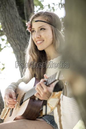 happy young woman playing guitar in