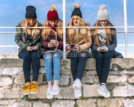 vier freunde sitzen seite an seite