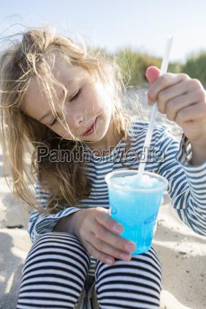 maedchen am strand ruehren blau gefrorenes