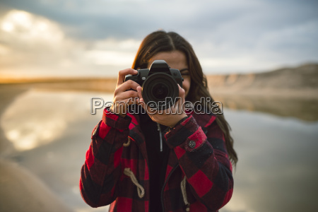young woman taking picture with camera