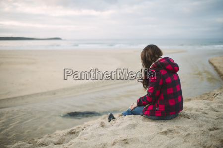 young woman on the beach looking