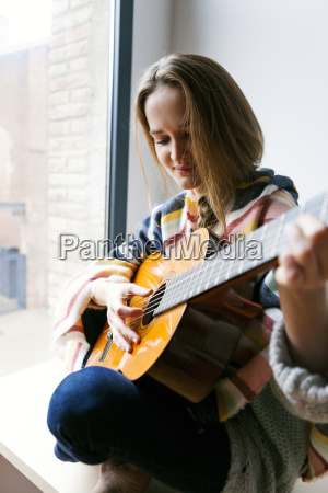 junge frau spielt gitarre