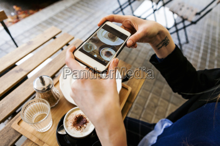woman in pavement cafe taking picture