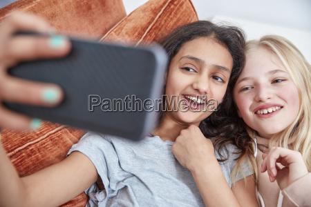 zwei glueckliche maedchen beim smartphone