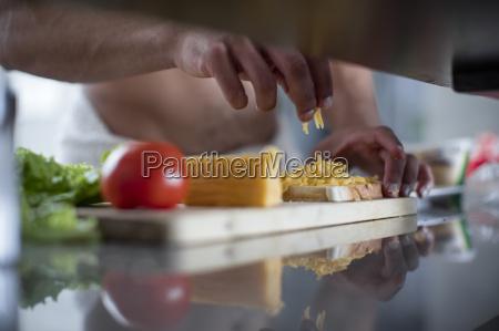mann bereitet ein kaese sandwich zu