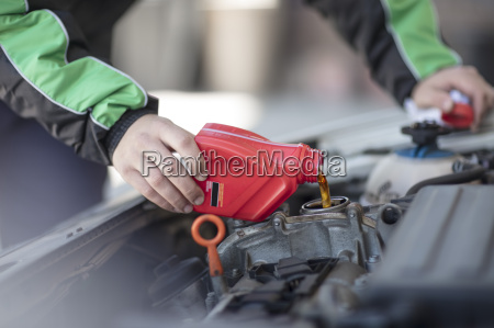 man filling up car with motor