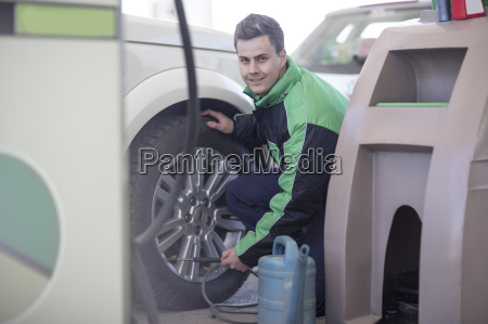 man filling car tyres with air