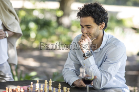 man playing game of chess thinking