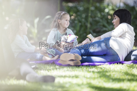 mother reading a book to children