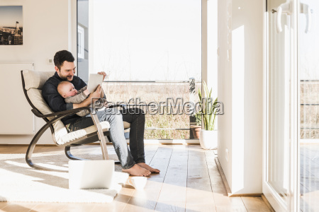 father sitting in arm chair with