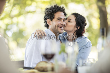 young woman kissing a happy young