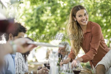 smiling woman dishing up at family