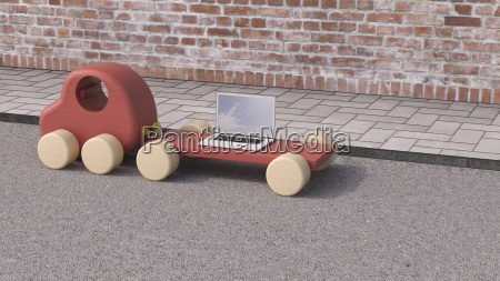 laptop on trailer of wooden toy