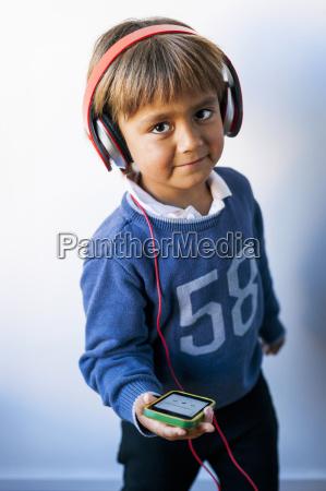 kleiner junge hoert musik seines smartphones