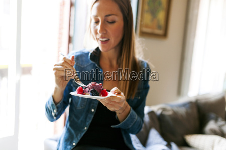 young woman eating a healthy dessert