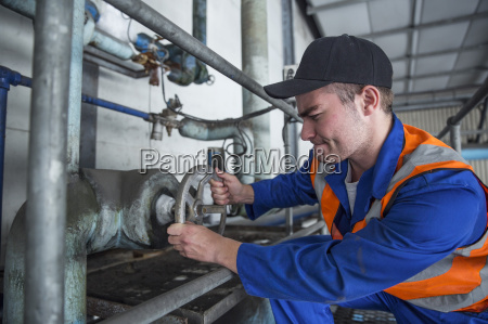 worker turning valve in factory