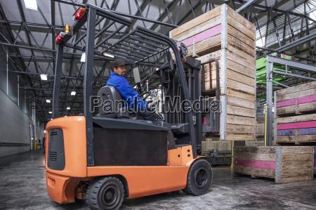 mann auf gabelstapler in fabrikhalle