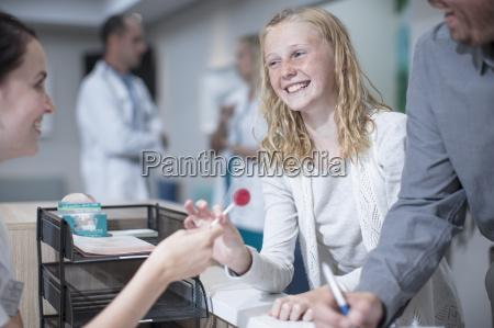 sick girl getting lollipop from receptionist
