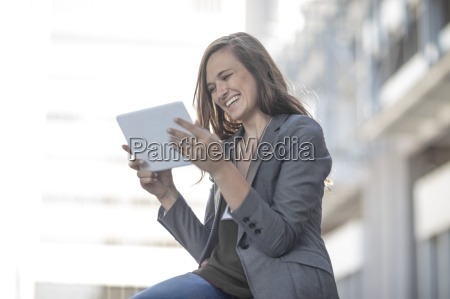 young laughing woman using digital tablet