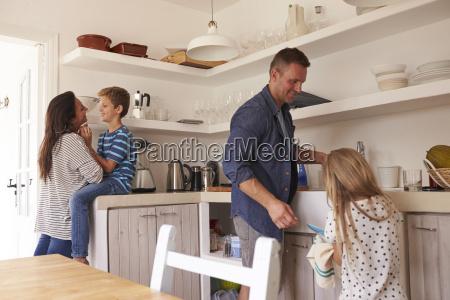 children helping parents in kitchen with