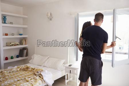couple by window in bedroom back