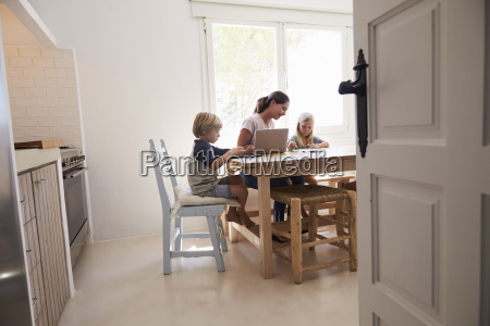 mum and two kids working at