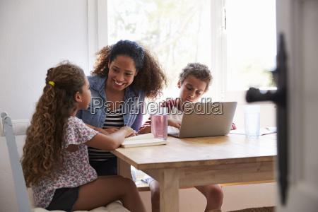 mum sitting with kids at kitchen