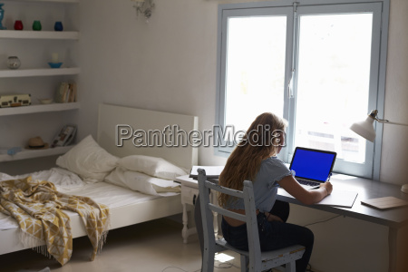 teenage girl working with laptop at