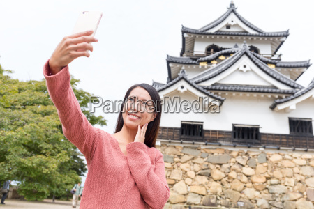 asian woman taking selfie by mobile