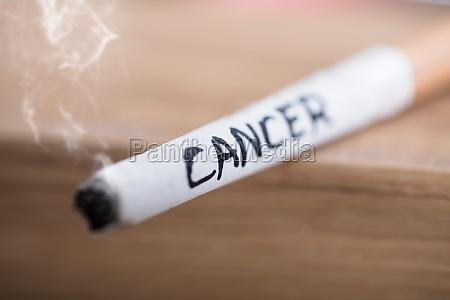 krebs text auf brennende zigarette