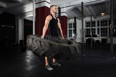man doing exercise with tire
