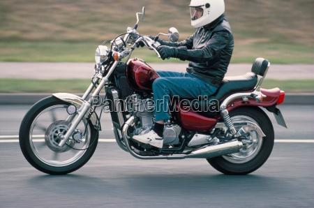 motorradfahrer faehrt suzuki twin motorrad auf