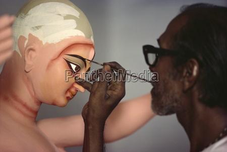 painting clay based image of durga